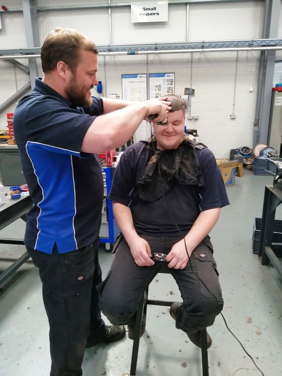 Apprentice Jason gets a haircut from workshop manager Steve