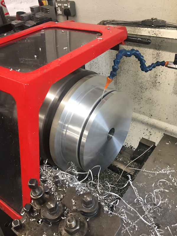 Machining a part on a lathe in our machine shop.